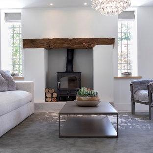 Idee per un soggiorno design di medie dimensioni e aperto con libreria, pareti bianche, pavimento con piastrelle in ceramica, stufa a legna, cornice del camino in intonaco, nessuna TV e pavimento bianco
