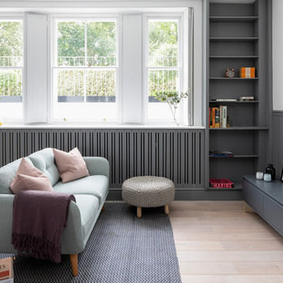 Scandinavian games room in London with a reading nook, multi-coloured walls, light hardwood flooring, no fireplace and beige floors.