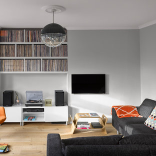 Design ideas for a medium sized contemporary family and games room in London with grey walls, no fireplace, a wall mounted tv, beige floors and light hardwood flooring.