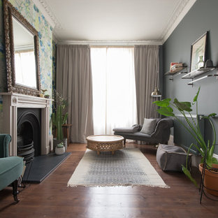 Inspiration for a medium sized classic games room in London with blue walls, medium hardwood flooring, a standard fireplace, a metal fireplace surround and brown floors.