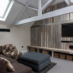 Inspiration for a rustic games room in Other with beige walls, carpet, a wall mounted tv and grey floors.