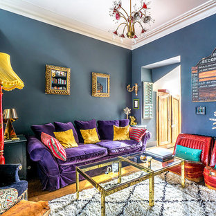 Example of an eclectic enclosed medium tone wood floor and brown floor family room design in London with blue walls
