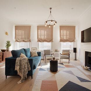 На фото: с высоким бюджетом открытые гостиные комнаты среднего размера в скандинавском стиле с белыми стенами, светлым паркетным полом, телевизором на стене, стандартным камином и фасадом камина из штукатурки