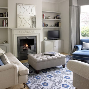 Inspiration for a small classic enclosed games room in Surrey with grey walls, light hardwood flooring, a standard fireplace, a stone fireplace surround, a freestanding tv and beige floors.