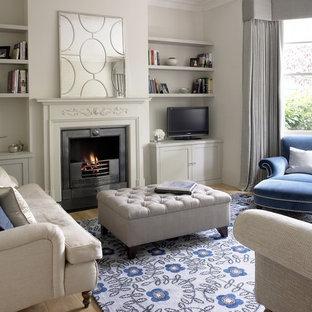 Ejemplo de sala de estar cerrada, tradicional, pequeña, con paredes grises, suelo de madera clara, chimenea tradicional, marco de chimenea de piedra, televisor independiente y suelo beige