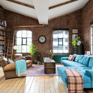 Großes Industrial Wohnzimmer mit roter Wandfarbe, braunem Holzboden und braunem Boden in London
