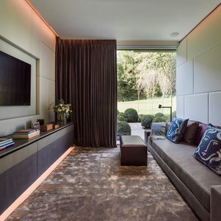 This is an example of a contemporary enclosed family and games room in London with beige walls and a wall mounted tv.