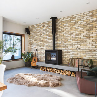 This is an example of a scandinavian open plan games room in London with a music area, white walls, concrete flooring, a wood burning stove and grey floors.