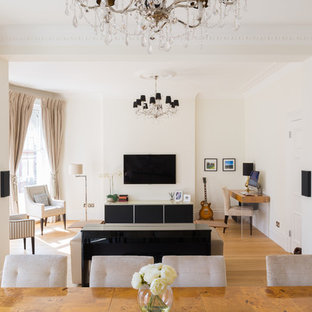 Design ideas for a traditional open plan family and games room in London with a music area, white walls, medium hardwood flooring and a wall mounted tv.