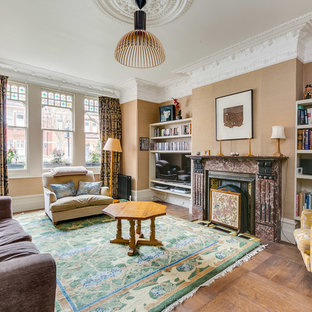 Design ideas for a medium sized classic family and games room in London with beige walls, medium hardwood flooring, a standard fireplace, a stone fireplace surround, a built-in media unit and brown floors.