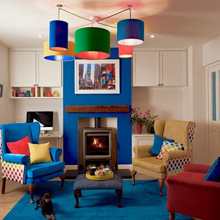 Medium sized eclectic enclosed games room in Berkshire with blue walls, vinyl flooring, a wood burning stove, a stone fireplace surround and brown floors.