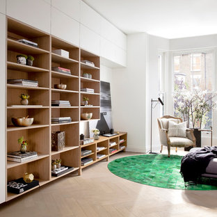 Photo of a medium sized contemporary open plan family and games room in London with white walls, light hardwood flooring, no tv and a reading nook.