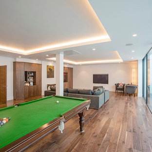 Photo of a large contemporary open plan family and games room in London with a game room, medium hardwood flooring, a wall mounted tv and white walls.