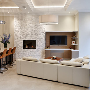 Design ideas for a contemporary open plan family and games room in Orange County with white walls, a standard fireplace, a stone fireplace surround and a wall mounted tv.