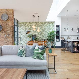 Ejemplo de sala de estar abierta, actual, con paredes multicolor y suelo de madera clara