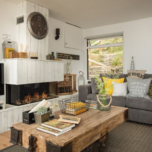 Design ideas for a medium sized coastal open plan family and games room in Cornwall with a home bar, white walls, medium hardwood flooring, a standard fireplace, a wooden fireplace surround, a freestanding tv and beige floors.