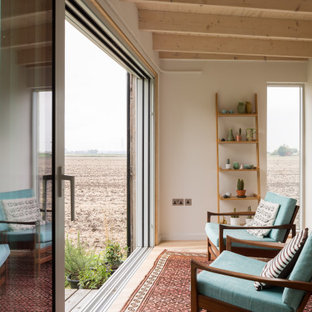Design ideas for a contemporary enclosed games room in Cambridgeshire with white walls, light hardwood flooring, no fireplace, no tv, beige floors and exposed beams.