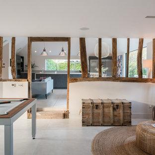 Imagen de sala de juegos en casa abierta, campestre, grande, con paredes blancas y suelo de piedra caliza