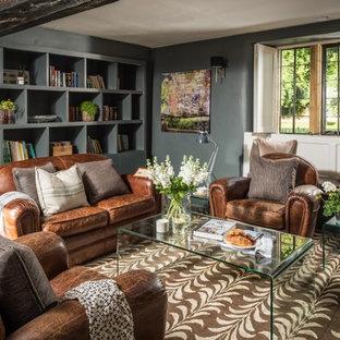 Inspiration pour une salle de séjour avec une bibliothèque ou un coin lecture traditionnelle de taille moyenne avec un mur vert, un sol en ardoise, un poêle à bois, un manteau de cheminée en pierre et un sol gris.