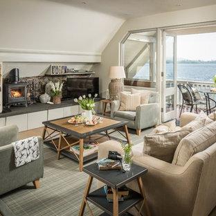 他の地域の大きいビーチスタイルのおしゃれなファミリールーム (白い壁、淡色無垢フローリング、薪ストーブ、石材の暖炉まわり、据え置き型テレビ、ベージュの床) の写真