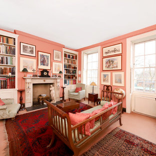 This is an example of a medium sized traditional enclosed games room in London with pink walls, no tv, a reading nook, a standard fireplace and pink floors.