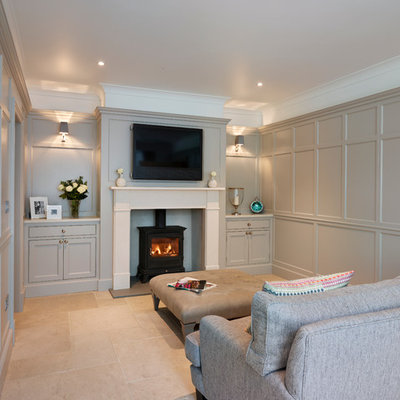 Example of a large trendy open concept family room design in Essex with gray walls, a standard fireplace and a wall-mounted tv