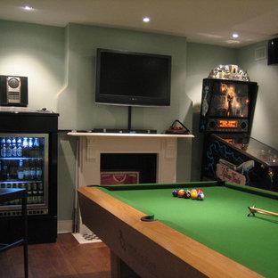 Esempio di un soggiorno moderno di medie dimensioni e chiuso con sala giochi, pareti blu, pavimento in legno massello medio, camino classico, cornice del camino in pietra e TV a parete