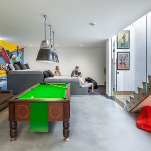Trendy concrete floor family room photo in Oxfordshire with multicolored walls and no fireplace