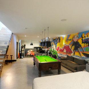 Cette photo montre une salle de séjour tendance avec un mur multicolore, béton au sol et aucune cheminée.