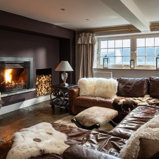 Photo of a large rural enclosed games room in Cornwall with brown walls, a wall mounted tv, grey floors and a standard fireplace.
