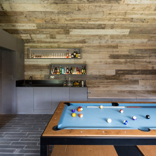 Design ideas for a contemporary games room in Hampshire with a game room, brown walls, grey floors, a vaulted ceiling and wood walls.