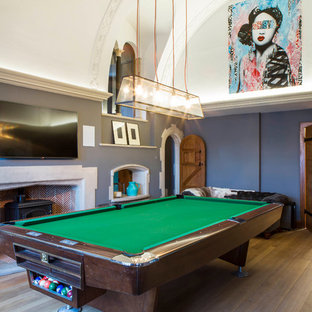 Photo of a large traditional enclosed family and games room in Oxfordshire with a game room, light hardwood flooring, a wood burning stove, a wall mounted tv and brown floors.