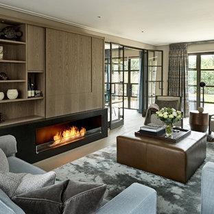 Ejemplo de sala de estar cerrada, contemporánea, de tamaño medio, con chimenea lineal y televisor retractable