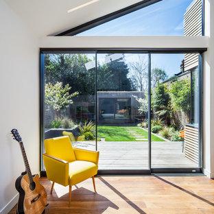 Пример оригинального дизайна: гостиная комната в современном стиле с музыкальной комнатой, белыми стенами и светлым паркетным полом