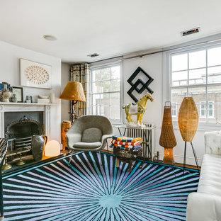 Cette image montre une salle de séjour bohème de taille moyenne et fermée avec un mur blanc, une cheminée standard, un manteau de cheminée en métal, un téléviseur fixé au mur, un sol en liège et un sol marron.