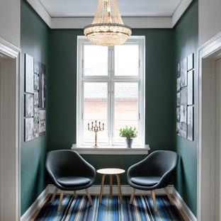 Inspiration pour un couloir traditionnel avec un mur vert et un sol en bois brun.