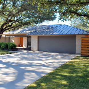 Example of a large minimalist attached two-car garage design in Austin