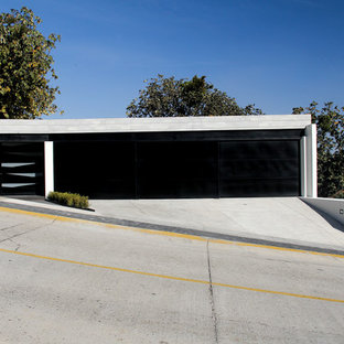 Inspiration for a huge contemporary attached three-car garage remodel in Other