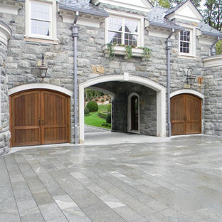 This is an example of a large arts and crafts attached two-car porte cochere in New York.