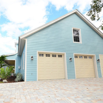 Example of a mid-sized island style attached two-car garage design in Miami