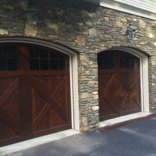 Example of a large mountain style attached three-car garage design in New York