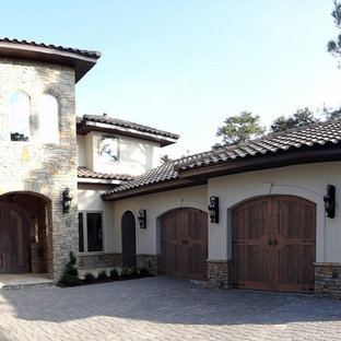 Inspiration for a large mediterranean attached three-car garage in Orlando.