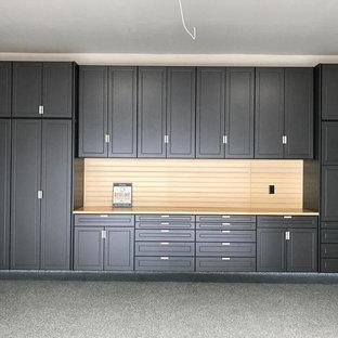 Réalisation d'un garage pour deux voitures attenant design de taille moyenne avec un bureau, studio ou atelier.