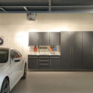 Exemple d'un très grand garage pour trois voitures attenant moderne avec un bureau, studio ou atelier.