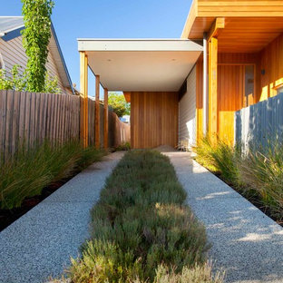 Design ideas for a small contemporary attached one-car carport in Melbourne.
