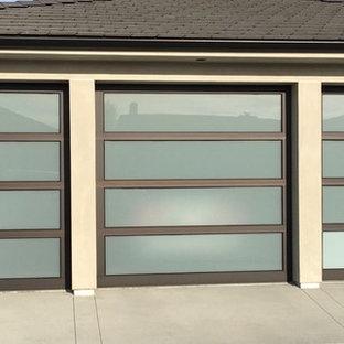 Exemple d'un grand garage pour trois voitures attenant moderne.