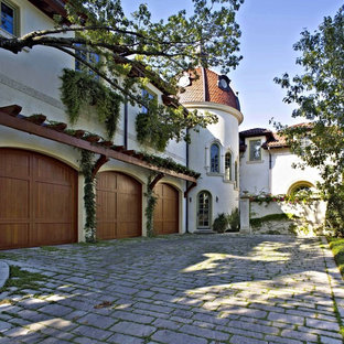 Example of a large tuscan attached three-car garage design in Dallas