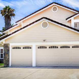 Design ideas for a shabby-chic style attached three-car garage in Orange County.