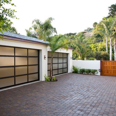 Example of a large island style attached two-car garage design in Santa Barbara