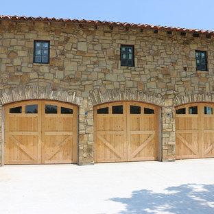 Garage - huge rustic attached three-car garage idea in Austin